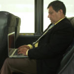 Man in Suit sitting in comfortable bus leather seat using laptop with WiFi