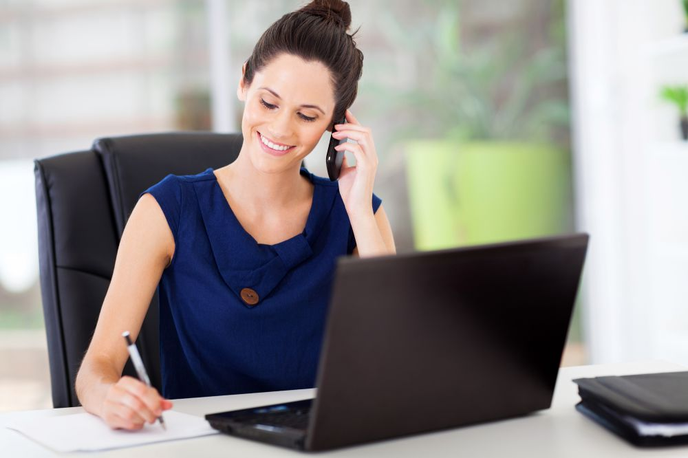 Lady Sales Representative Smiling Talking On The Phone. Writing with a pen on a paper. She has her laptop open on her white desk.
